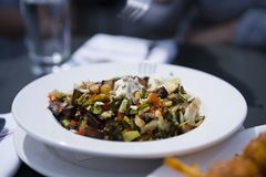 与切成小方块的菜和乳酪-真正的f的可口被烘烤的土豆 免版税库存图片