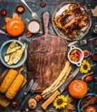 与切板、烤有机收获菜、南瓜、整个火鸡或者ch的秋天季节性烹调和吃背景 免版税库存图片
