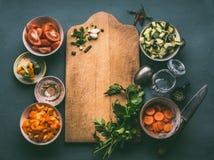 与切板的健康食物背景,各种各样的新鲜的切成小方块的菜成份、匙子和玻璃为做的午餐,上面刺激 免版税图库摄影