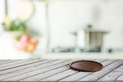 与切板的空的木桌面和显示或蒙太奇的defocused现代厨房您的产品 免版税图库摄影