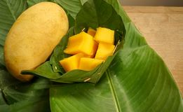 与切片的一个黄色芒果以绿色已经离开篮子 库存照片