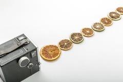 与切片的减速火箭的照相机干桔子 免版税库存图片