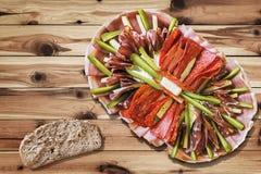 与切片的开胃菜盘Meze在土气被打结的松木庭院表上的整粒面包集合 免版税库存图片