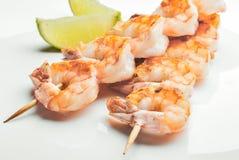 与切片的烤虾在白色盘的石灰 免版税图库摄影
