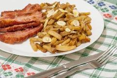 与切片的青豆油煎的烟肉和装饰用切片在白色板材的大蒜在装饰的桌布 免版税库存照片