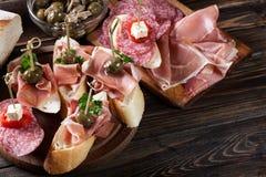 与切片jamon serrano、蒜味咸腊肠、橄榄和乳酪立方体的西班牙塔帕纤维布在一张木桌上 库存图片