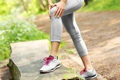 与创伤膝盖的慢跑者 免版税库存照片