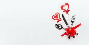 与利器和红色丝带的欢乐桌在白色背景,横幅的餐位餐具和心脏 免版税图库摄影
