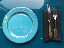 与利器的一个美丽的光滑的浅兰的盘在一块黑暗的餐巾 免版税库存图片