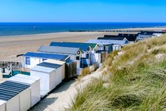 与别墅、沙丘、空的海滩、蓝色海和清楚的天空的沿海看法 免版税库存图片