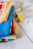 与别针、测量的磁带和滚动的棉花的五颜六色的织品 库存照片
