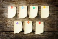 与别针overWeekly稠粘的笔记的稠粘的笔记与在木背景的五颜六色的别针 免版税库存照片