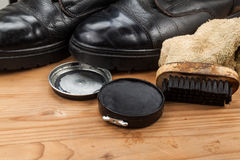 与刷子、布料和破旧的起动的鞋子上光剂在木平台 库存照片