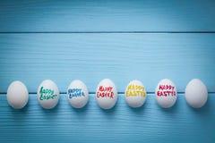 与刷子写的颜色标题`愉快的复活节`的复活节彩蛋在与小插图作用的蓝色色的木背景 免版税库存图片