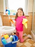 与刷子和旧布的微笑的女孩清洁洗手间 库存图片