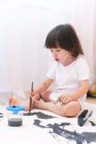 与刷子和树胶水彩画颜料的小孩油漆在家 免版税库存图片