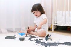 与刷子和树胶水彩画颜料的小孩绘画在家 库存图片