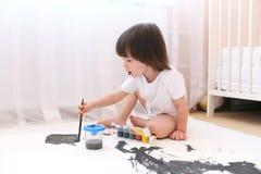 与刷子和树胶水彩画颜料的小孩绘画 免版税库存图片
