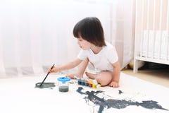 与刷子和树胶水彩画颜料的小男孩油漆 免版税图库摄影