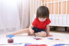 与刷子和树胶水彩画颜料的逗人喜爱的可爱的儿童绘画 库存图片