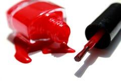 与刷子和瓶的溢出的指甲油搪瓷红色在白色背景 免版税库存照片