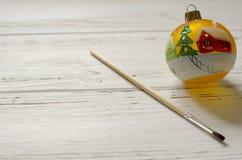 与刷子的手画新年球在白色木背景 免版税图库摄影