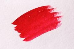 与刷子的红色冲程由水彩做成 背景接近的纸射击 B 免版税库存照片
