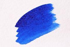 与刷子的蓝色冲程由水彩做成 背景接近的纸射击 免版税图库摄影