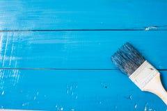 与刷子的蓝色油漆在木头 库存照片