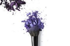 与刷子的被击碎的紫色化妆粉末 库存图片