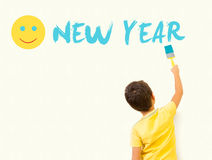 绘与刷子的逗人喜爱的小男孩新年好在墙壁上 库存照片