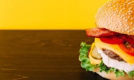 与剁的明亮的水多的开胃汉堡,乳酪,用了卤汁泡黄瓜、蕃茄和烟肉 免版税库存图片