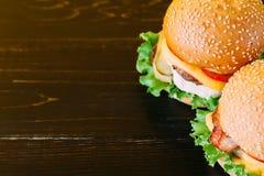与剁的明亮的水多的开胃汉堡,乳酪,用了卤汁泡黄瓜、蕃茄和烟肉 库存照片