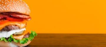与剁的明亮的水多的开胃汉堡,乳酪,用了卤汁泡黄瓜、蕃茄和烟肉 免版税库存照片