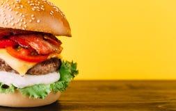 与剁的明亮的水多的开胃汉堡,乳酪,用了卤汁泡黄瓜、蕃茄和烟肉 库存图片