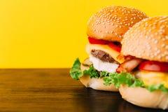 与剁的明亮的水多的开胃汉堡,乳酪,用了卤汁泡黄瓜、蕃茄和烟肉 免版税图库摄影