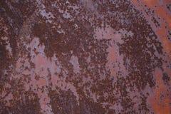 与剥红色油漆的生锈的破旧的金属板料 金属纹理 库存图片