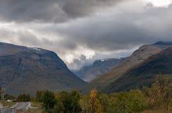 与剧烈的云彩和一条偏僻的路的挪威山风景 免版税图库摄影
