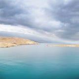 与剧烈的云彩的风平浪静小海湾 库存照片