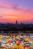 与剧烈的多个颜色城市夜市场在日落天空背景以后 免版税库存图片