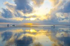 与剧烈的天空和小船的日出 库存图片