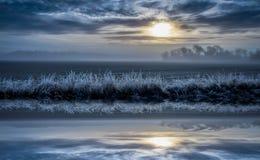 与剧烈的天空的冷的有雾的风景,反射在水中 库存图片