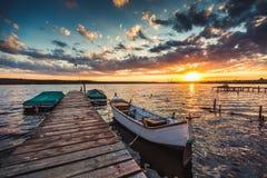 与剧烈的天空的平安的日落和小船和跳船 免版税库存照片