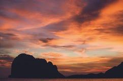 与剧烈的天空的热带海岛日落 免版税库存照片