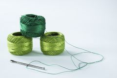与剪刀和针的绿色钩针编织毛线 白色背景, 图库摄影