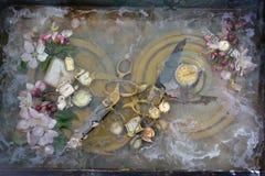 与剪刀的原始的艺术静物画:两把剪刀埋头苦干把柄和谎言在一个圆的黄铜名牌在花中 库存图片