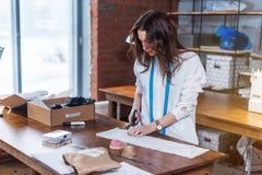与剪刀的年轻女性时装设计师切口织品在演播室 免版税图库摄影