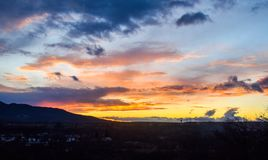 与剪影林木线和火云彩的多色的日落 图库摄影