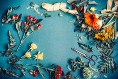 与剪的各种各样的秋天花和叶子安排做在蓝色桌背景,顶视图,框架的装饰花束的 免版税库存图片