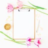 与剪贴板、笔记本、桃红色郁金香和辅助部件的自由职业者或博客作者工作区在白色背景 平的位置,顶视图 库存图片